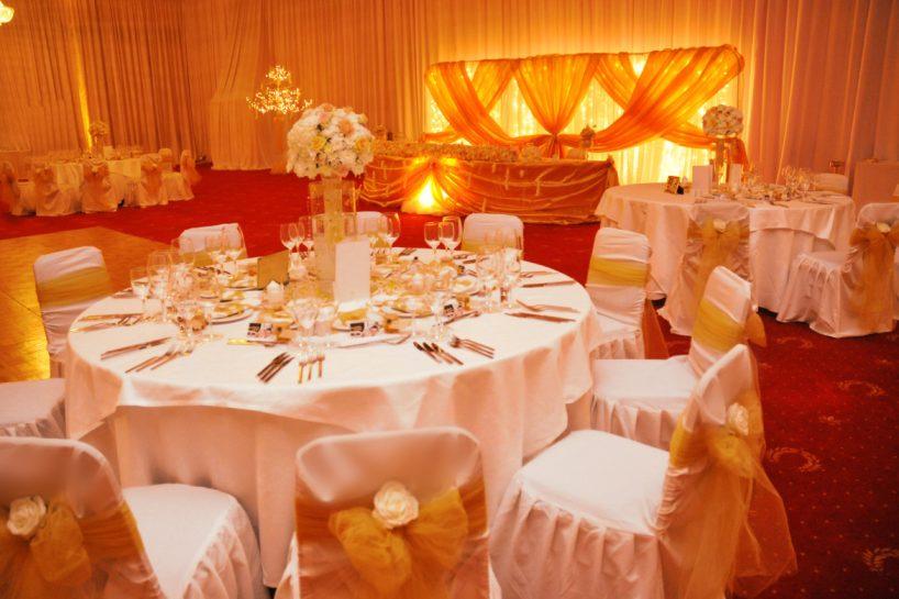 Сватбена украса в София хотел Маринела в златно с осветление uplight от земята на залата от сватбена агенция, декорация на сватба със златни панделки за столове и бели калъфи за столове за сватба, висока ваза с цветя за масите на гостите и плуващи рибки