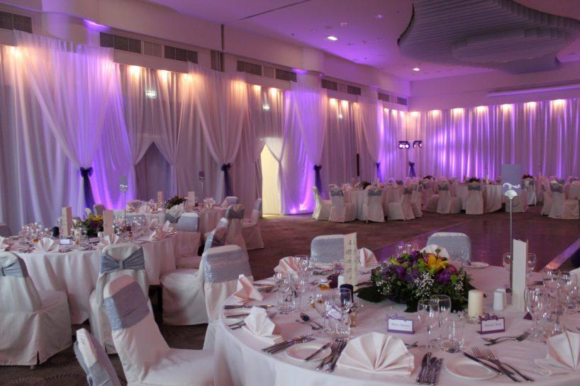 Сватбена украса в София хотел Хилтън в лилаво с осветление uplight от земята на залата от сватбена агенция, обличане на стените с плат в зала Мусала Hilton, декорация на сватба със сребърни панделки за столове и украса с цветя на масите на гостите