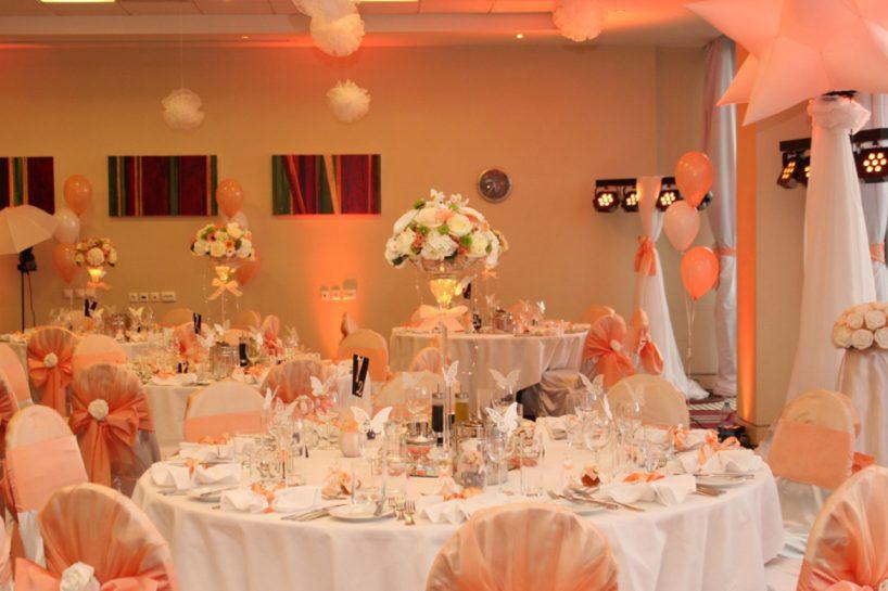 Сватбена украса в София хотел Холидей Инн в прасковено с осветление uplight от земята на залата от сватбена агенция, обличане на стените с плат в зала в Holiday Inn, декорация на сватба със прасковени панделки за столове и бели калъфи за столове за сватба, висока ваза с цветя за масите на гостите