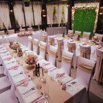 Сватбена украса в хотел All Seasons София ленено на тераса навън, стена за снимки със зеленина и цветя, ластични калъфи за столове и ленени панделки за столове за сватба, букети с естествени цветя за масите на гостите