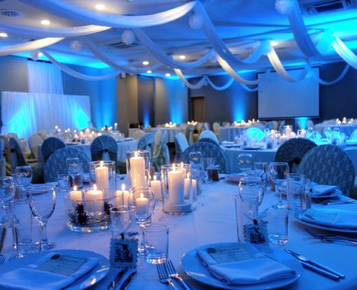 Сватбена украса в хотел Премиер Летище София в светло син цвят с осветление от земята на залата от сватбена агенция, декорация на тавана на залата с платове и воали за сватба в Premier Best Western със сватбена тема шишарки и свещи, екрю дантела за столове, вази цилиндър със свещи за сватба, тема зимна сватба