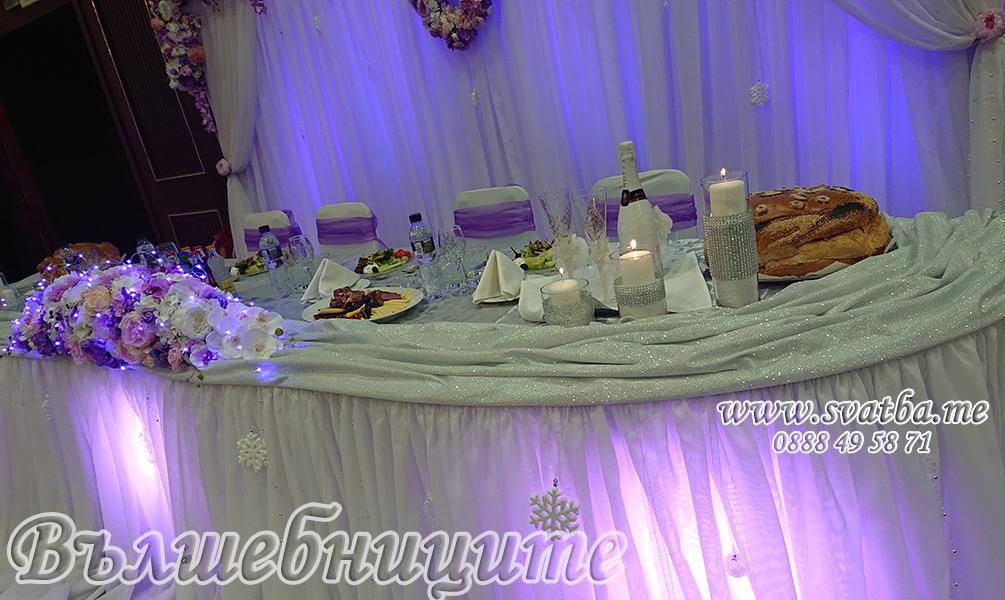 Сватбена украса в София хотел Маринела Hotel Marinela Sofia wedding в лилаво с осветление uplight от земята на залата от сватбена агенция, декорация на сватба с лилави панделки за столове и бели калъфи за столове за сватба, висока ваза с изкуствени цветя за маса, украса на сватбената маса с букет цветя