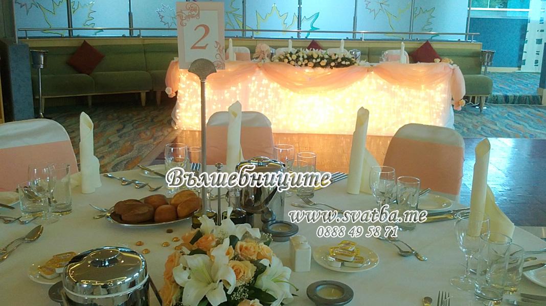 Сватбена украса в хотел Хилтън за сватба в прасковено с прасковени панделки на столовете и декорация на сватбена маса